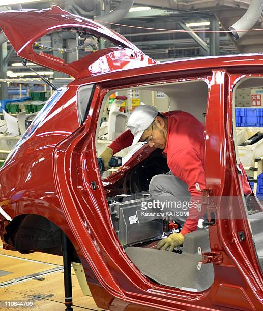 Japanese Nissan Factory In Oppama Japan On January 24 2011 A worker installs battery chargers in car bodies of Nissann electric vehicle Leaf on its...