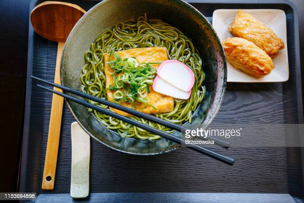 japanese noodle soup with green soba noodles, deep fried tofu and inarizushi as a side dish. - soba stock pictures, royalty-free photos & images