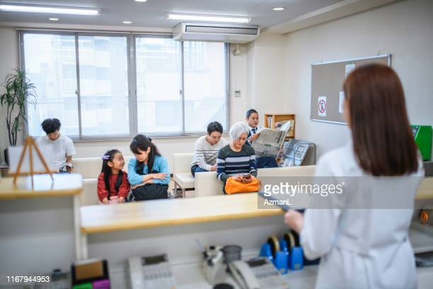 japanese nurse and patients in tokyo hospital waiting room - outpatient care stock pictures, royalty-free photos & images