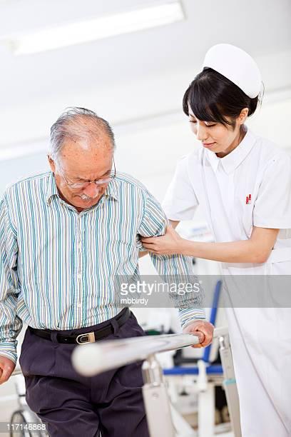 日本の看護師トレーニングをする老人男性 paralel バー - 単語 help ストックフォトと画像