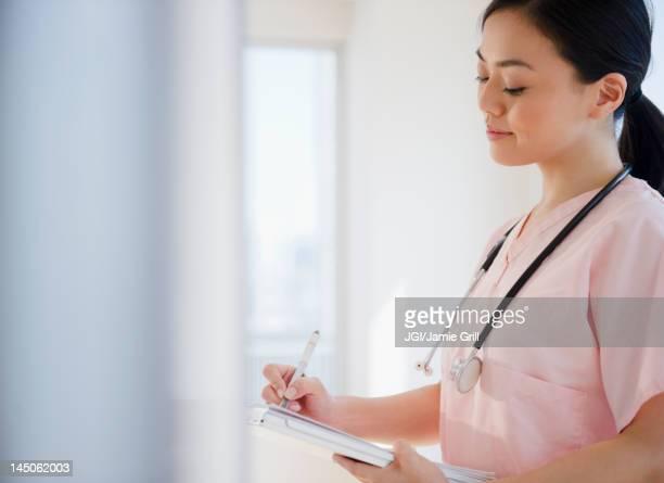 Japanese nurse writing on medical record