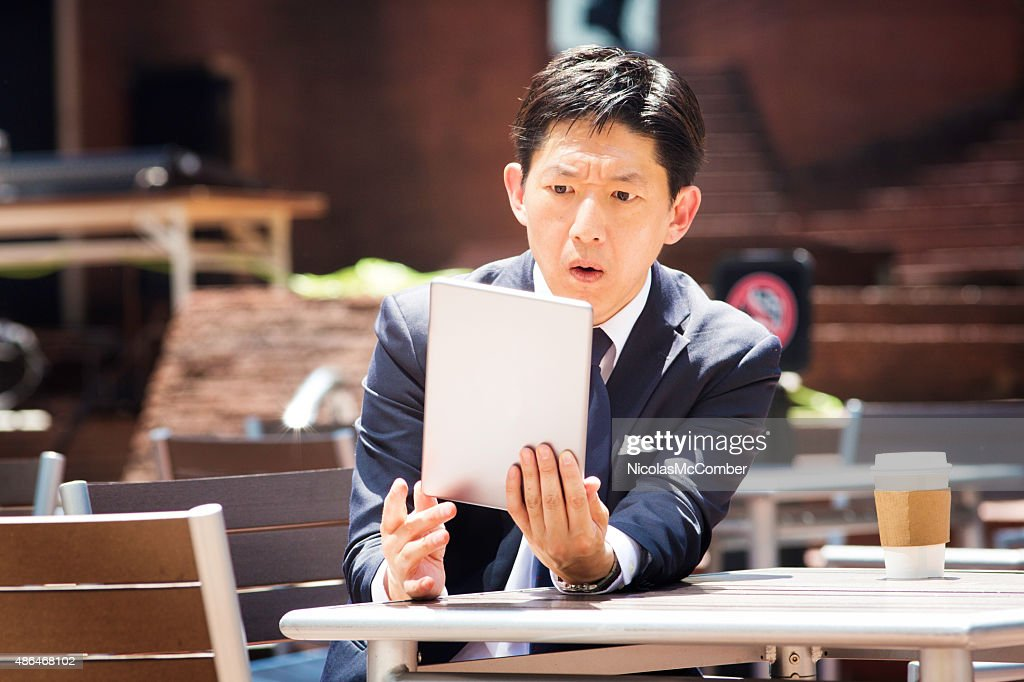 日本の会社員的なニュースを読むタブレット屋外 : ストックフォト