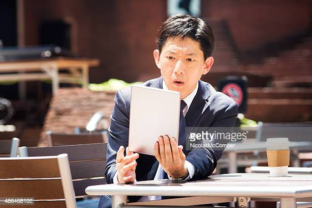 Japanese office worker reads shocking news on tablet outdoors