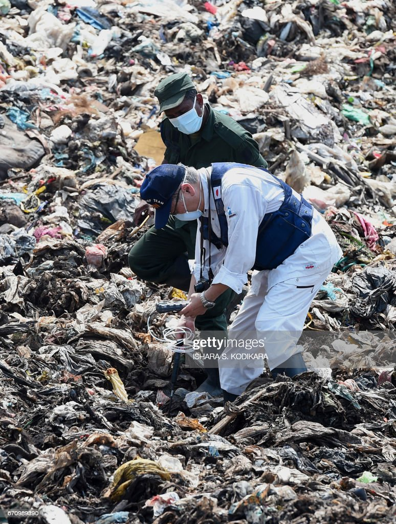A Japanese official with a disaster relief team surveys the site of a garbage dump collapse that killed 32 people on the northeastern edge of Sri Lankas capital Colombo on April 21, 2017. A Japanese disaster relief team is advising the Sri Lankan government on measures to deal with the huge rubbish dump and relocate hundreds of families in the neighbourhood following the disaster. / AFP PHOTO / Ishara S. KODIKARA