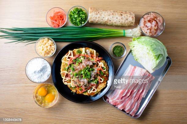japanese okonomiyaki recipe. a collection of finished okonomiyaki served on a black plate and ingredients such as pork, cabbage, yam, skipjack and eggs. the background is a light brown table. - tenkasu stock pictures, royalty-free photos & images