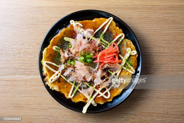 japanese okonomiyaki recipe. okonomiyaki served on a black plate on a wood grain table. put mayonnaise and bonito, red ginger and seaweed. - tenkasu stock pictures, royalty-free photos & images