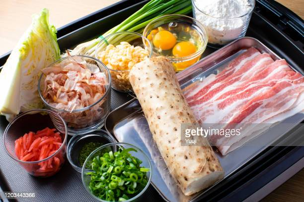 japanese okonomiyaki recipe. on the hot plate, there are ingredients of yam, flour, cabbage, pork, tenkasu, egg, red ginger, bonito, green seaweed, and green onion. - tenkasu stock pictures, royalty-free photos & images