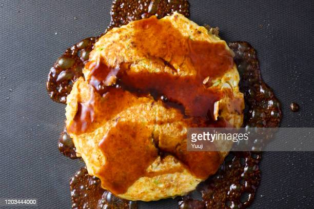 japanese okonomiyaki recipe. put the sauce on the okonomiyaki grilled on the hot plate. - okonomiyaki stock pictures, royalty-free photos & images