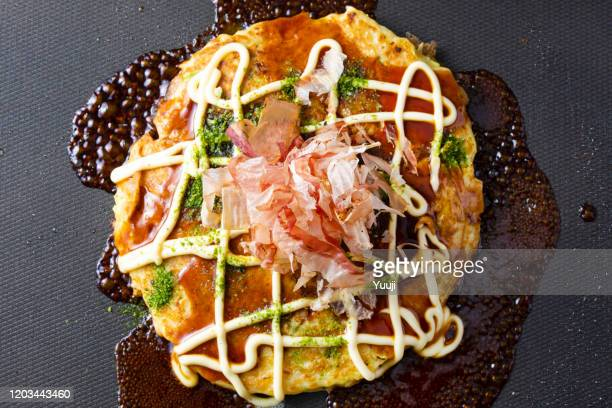 japanese okonomiyaki recipe. sprinkle sauce, mayonnaise, seaweed and bonito on okonomiyaki grilled on a hot plate. - okonomiyaki stock pictures, royalty-free photos & images