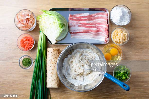 japanese okonomiyaki recipe. the ingredients of yam, flour, cabbage, pork, tenkasu, egg, red ginger, katsubushi, blue seaweed, green onion are placed on the wood grain table. melted flour in a stainless steel bowl. - tenkasu stock pictures, royalty-free photos & images