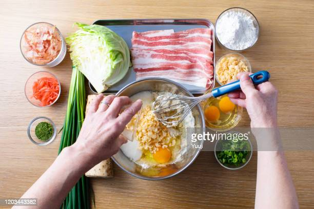 japanese okonomiyaki recipe. the ingredients of yam, flour, cabbage, pork, tenkasu, egg, red ginger, katsubushi, blue seaweed, green onion are placed on the wood grain table. my grandmother puts a cake in a stainless steel bowl. - tenkasu stock pictures, royalty-free photos & images