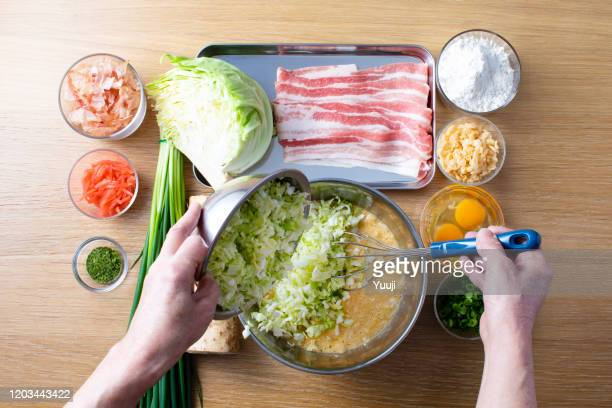 japanese okonomiyaki recipe. the ingredients of yam, flour, cabbage, pork, tenkasu, egg, red ginger, katsubushi, blue seaweed, green onion are placed on the wood grain table. my grandmother shreds cabbage into a heavenly cake, eggs, flour, yam and a stain - okonomiyaki stock pictures, royalty-free photos & images