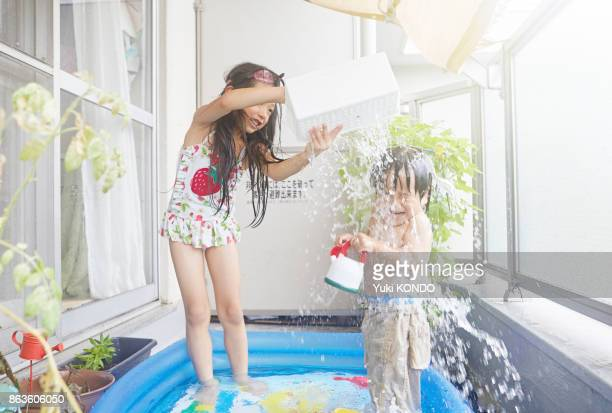 Japanese older sister and brother playing in plastic pool