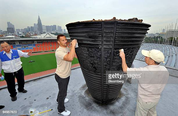 Japanese Olympic hammer throwing gold medalist Koji Murofushi, center, polishes the 1964 Tokyo Olympic Games cauldron at the site of the opening...