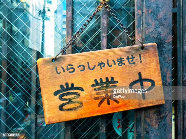 Japanese open sign hanging on the door of a store