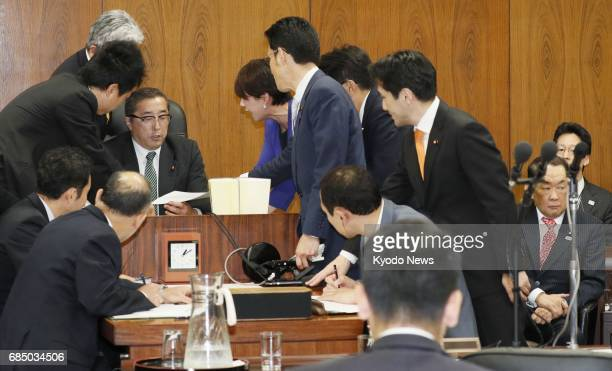 Japanese opposition lawmakers storm the podium of Junji Suzuki chairman of the House of Representatives' Committee on Judicial Affairs in Tokyo on...