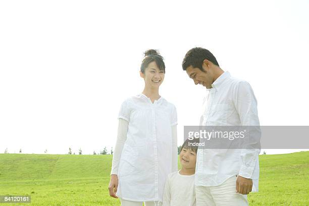 Japanese parents and boy standing on field