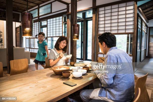 Japanese parents sitting at dinner table, daughter in background