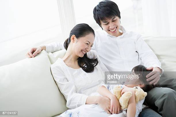 Japanese parents with daughter relaxing on couch