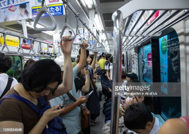 Japanese passengers in the subway using their mobile phones Kanto region Tokyo Japan on August 26 2018 in Tokyo Japan