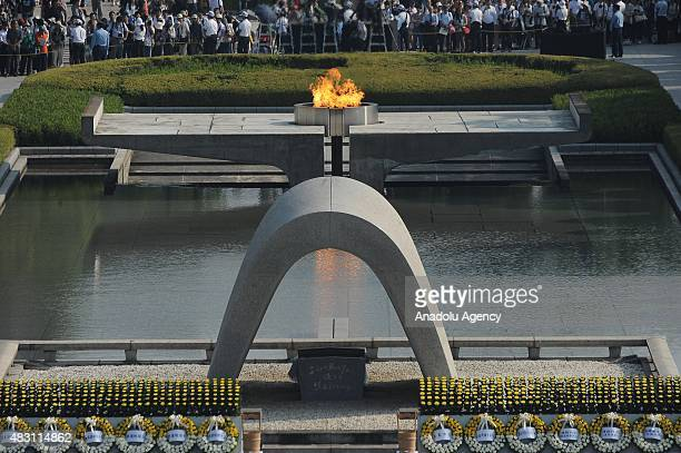 Japanese people are seen praying in front of the Cenotaph for the Bomb Victims after the Hiroshima Peace Memorial Ceremony at the Hiroshima Peace...