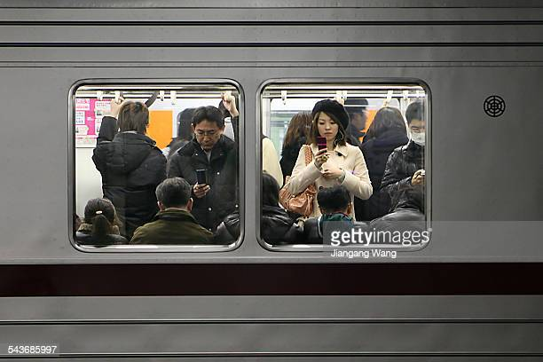 Japanese people are using mobile phones on a train.