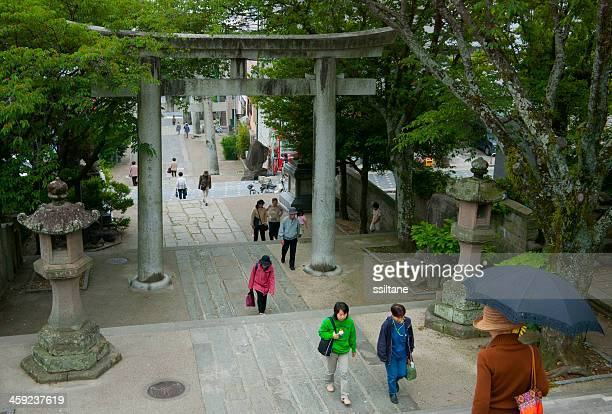 japanese people entering shinto shrine - shinto shrine stock pictures, royalty-free photos & images