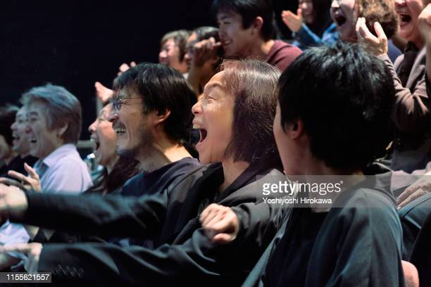 japanese people laughing watching a comedy at the theater - コンサートホール ストックフォトと画像