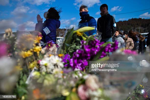 Japanese people pay their respect in front of the remaining structure of a former disaster center as they commemorate the second anniversary of the...