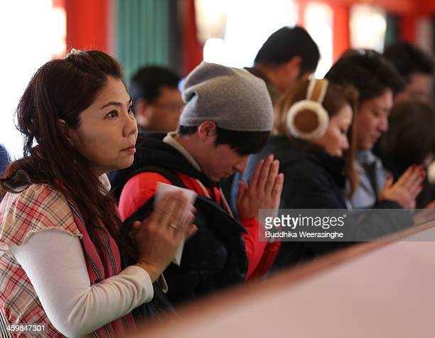 Japanese people pray to mark New Year's day during the celebration of 'Year of the Horse' at Ikuta Shrine on January 1 2014 in Kobe Japan Japanese...