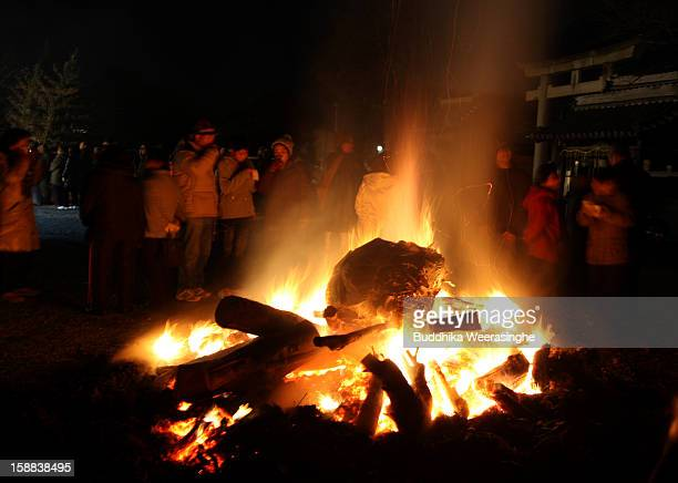 Japanese people stand close to a fire to warm up during the New Year blessing at the Sagamiji Buddhist temple on January 1 2013 in Kasai Japan...