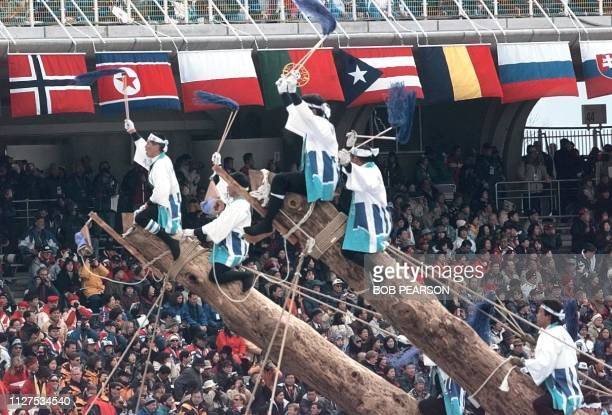 Japanese performers ride on the top of posts as they are raised to an upright position during the opening ceremonies of the XVIII Winter Olympics in...