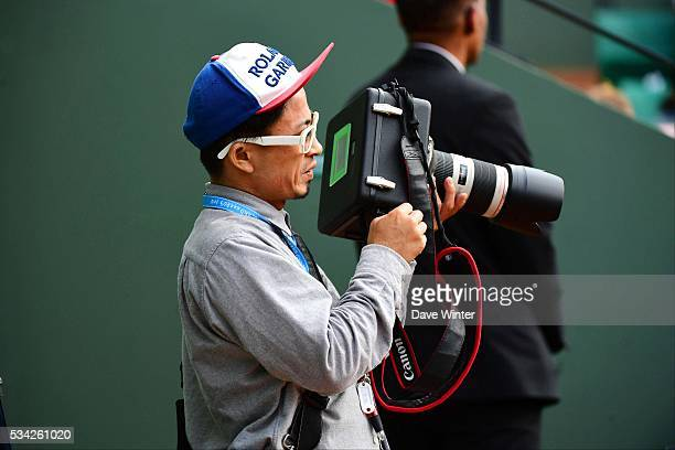A Japanese photographer uses a soundproof box to muffle the sound of his camera during the Women's Singles second round on day four of the French...