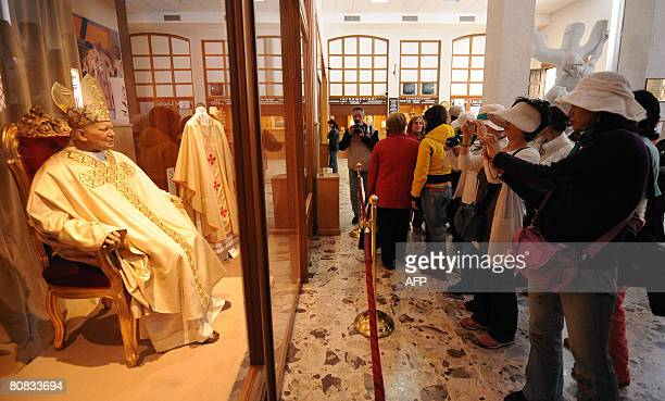 Japanese pilgrims take pictures of a statue of Pope John Paul II in the old Church of St Mary of Grace at San Giovanni Rotondo in the Puglia region...