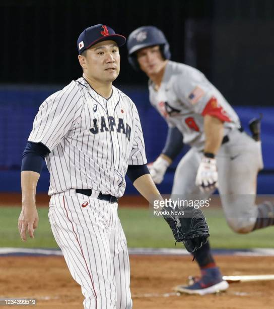 Japanese pitcher Masahiro Tanaka allows a game-tying single to Mark Kolozsvary of the United States in the fourth inning of their Tokyo Olympic...
