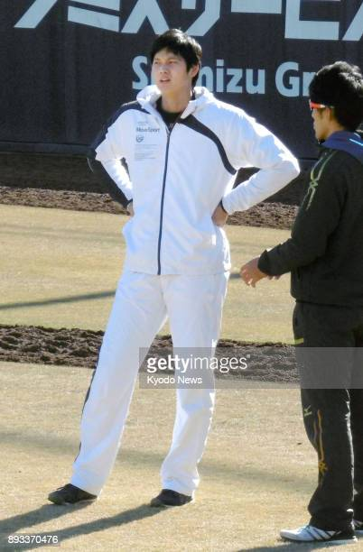 Japanese pitcherslugger Shohei Ohtani talks with a member of the Nippon Ham Fighters' staff at a training facility in Kamagaya Chiba Prefecture on...