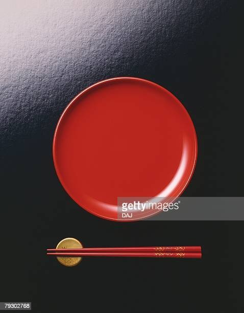 Japanese plate and chopsticks on holder, high angle view, black background
