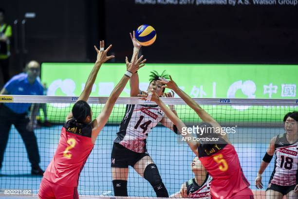 Japanese player Ayaka Matsumoto hits the ball while Chinese players Zhu Ting and Gao Yi try to block at the Women's Volleyball World Grand Prix in...