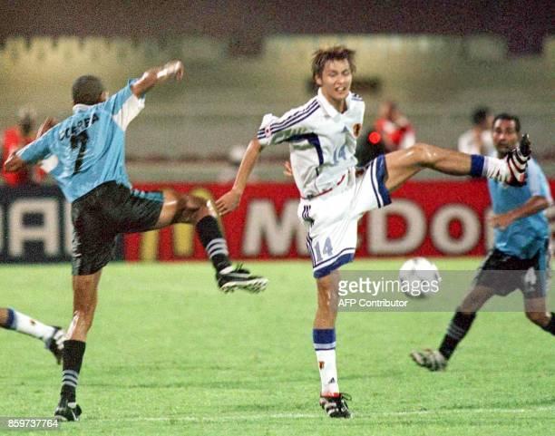 Japanese player Nagai Yuichiro battles for the ball against Uruguay player Correa Rodriguez Japan beat Uruguay 21 to qualify for the final against...