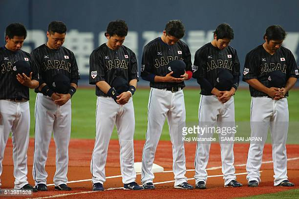 Japanese players and coaching staffs observe a minute of silence for the victims of the Great East Japan Earthquake firve years ago and the Tainan...