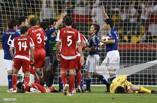 Japanese players and Syrian players remonstrate with the referee after Japanese goalkeeper Eiji Kawashima brought down Sanharib Malki of Syria during...