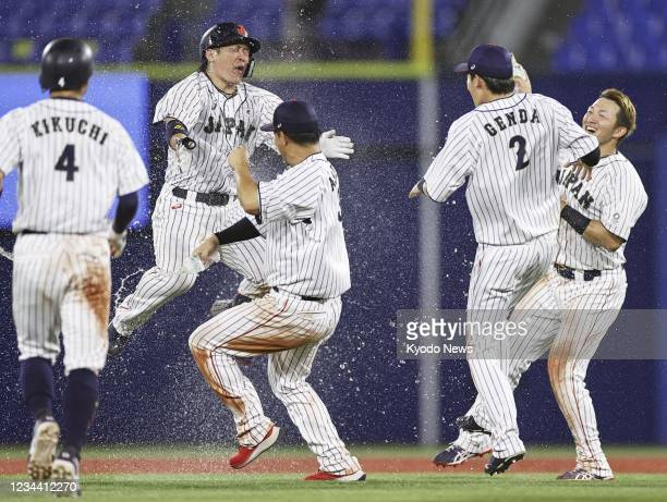 Japanese players celebrate after the game-winning hit by Takuya Kai in the 10th inning of their Tokyo Olympic second-round game against the United...