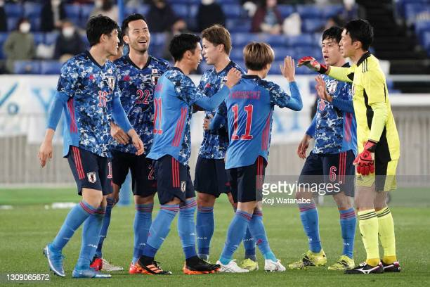 Japanese players celebrate their 3-0 victory in the international friendly match between Japan and South Korea at the Nissan Stadium on March 25,...