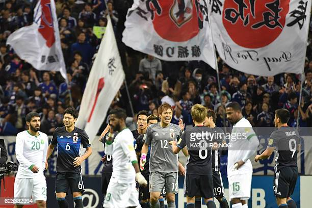Japanese players celebrate their victory over Saudi Arabia after their football match in Group B of the 2018 World Cup Asian qualifier at Saitama...