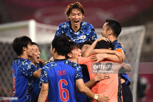 Japanese players celebrate with Kosei Tani who saves the penalty kick in the penalty shoot out during the Men's Quarter Final match on day eight of...