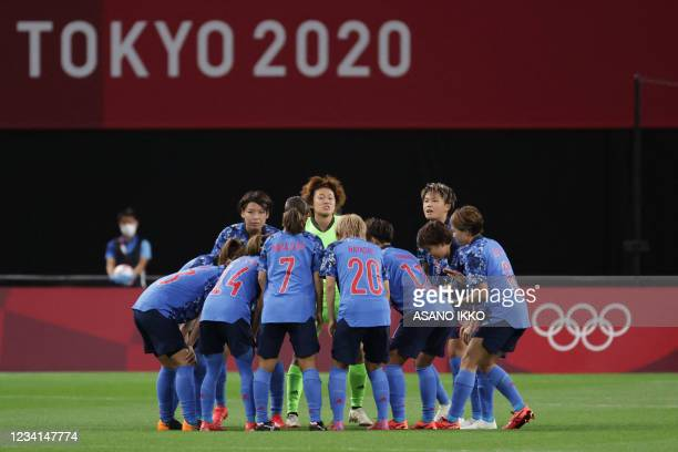 Japanese players gather in a huddle before the start of the Tokyo 2020 Olympic Games women's group E first round football match between Japan and...