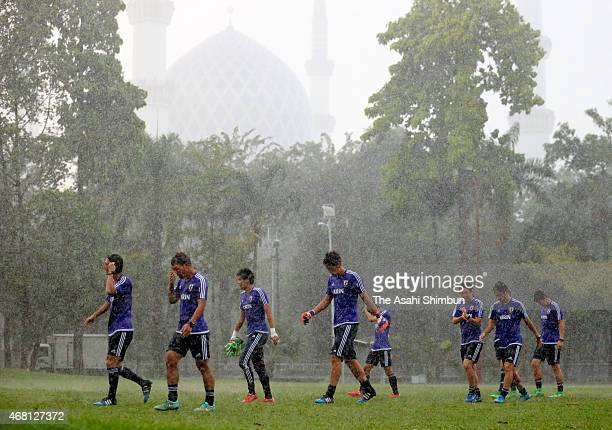 Japanese players leave a field as a training session is cancelled due to the heavy rain ahead of the AFC U23 Asian Cup qualifier match against...