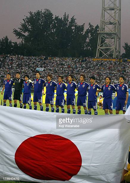 Japanese players line up during the national anthem prior to the 2014 FIFA World Cup Asian third round group C qualifying match between Uzbekistan...