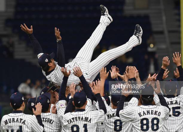 Japanese players tosses their playing manager Atsunori Inaba into the air to celebrate their victory after the final match against South Koreea in...