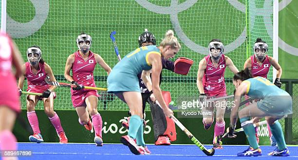 Japanese players wearing masks defend the goal in the face of a shooting attempt during the third quarter of a women's preliminary round hockey match...